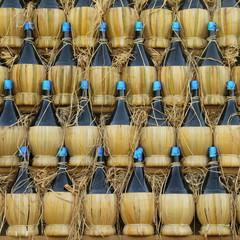 arranged many chianti wine bottles