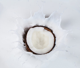 Coconut falling into milk splashes