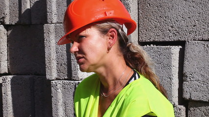 Worried woman-builder dressed in helmet and vest