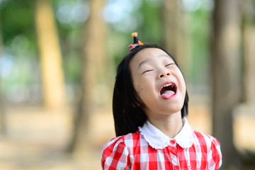 Happy Asian girl open her mouth outdoor.