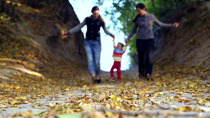 Mum walks with the child in the autumn forest.