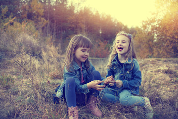 Two young girls amused at autumn sunny day