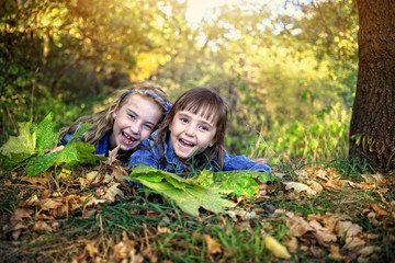 Girls lie under a tree with autumn leaves