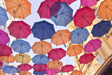 Colorful umbrellas over old building and sky