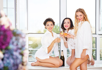Bride to be and bridal friends holding glass with champagne