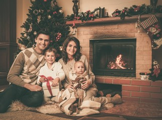 Family near fireplace in Christmas decorated house