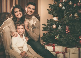 Happy family near Christmas tree in house interior