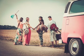 Multi-ethnic hippie friends with guitar and luggage