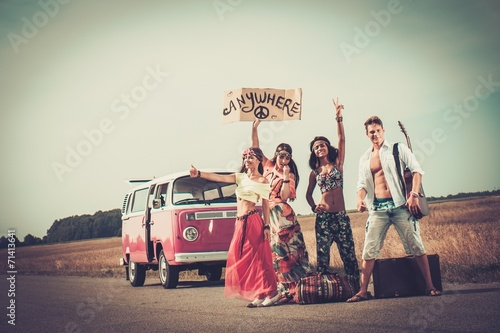 Multi-ethnic hippie hitchhikers with guitar and luggage  - 71413641