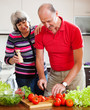 Loving mature couple cutting vegetables