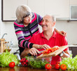 happy  elderly couple cooking  in kitchen
