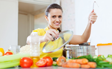 woman cooking  vegetarian food in saucepan