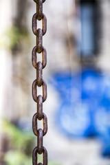 Rusty chain with grafitti bokeh