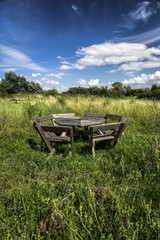 Rustic wooden picnic bench in meadow under blue sky