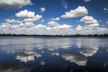 White fluffy clouds reflecting in a lake