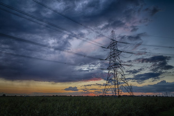 Electricity pylon at dusk and storm on the horizon
