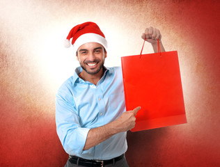 happy young handsome man wearing santa hat holding red shopping