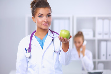 Female doctor hand holding a green apple, standing in office