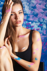 Young woman sitting near painting wall