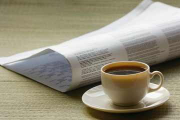 Coffee cup and newspaper.