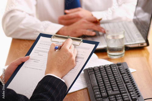 canvas print picture Businesspeople sitting at a table and signing a contract.