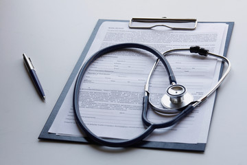 Medical clipboard and stethoscope isolated on white