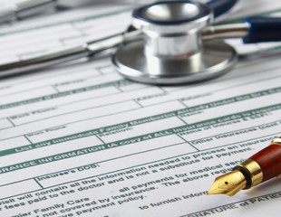 Stethoscope on medical billing statement on table, all text is