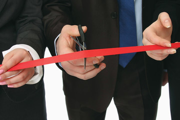 Business people cutting a red ribbon with a pair of scissors,