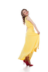 Happy young model posing in trendy yellow dress
