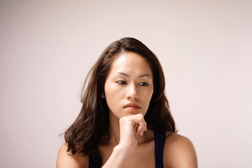 Asian chinese lady in deep thought with pink background