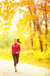 Athlete runner woman running in fall autumn forest
