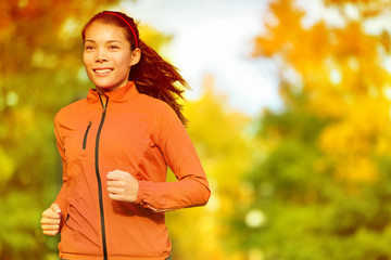 Runner woman running in fall autumn forest