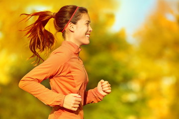 Woman runner running in fall autumn forest