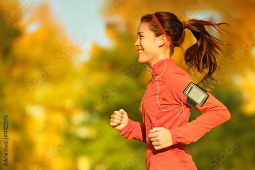 Fototapeta Woman runner running in fall autumn forest