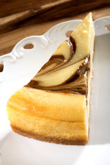 Cheesecake with caramel in white plate on a wooden brown table.