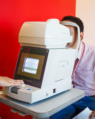 Young Optometrist measuring patient's eye pressure with tonomete