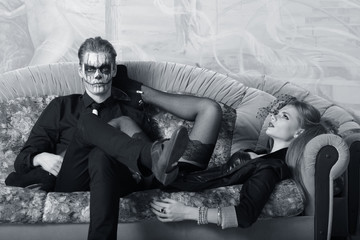 young man and woman on the sofa. makeup in Halloween theme
