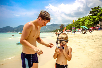 father adjusting his son's snorkel and mask before swimming