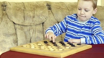 little boy plays checkers with his grandmother