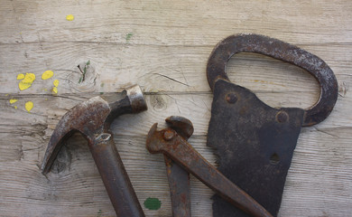 Ancient tools: saw, pincers, hammer on a old wooden background