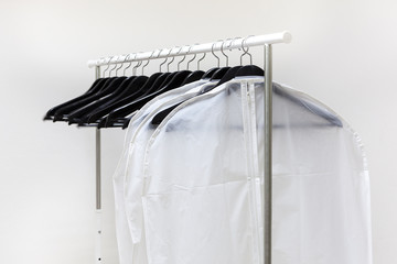 Clothes bags and hangers are on rack