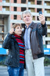 Mature man and woman making selfie with house key in hand