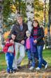 Four people family full length portrait in autumn park