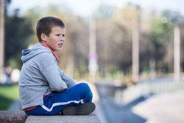 Thoughtful boy sitting on edge of granite plate, looks distance