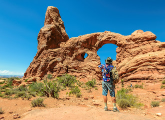 Tourist takes a picture Turret Arch in Arches National Park