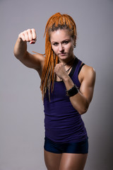 Young woman with dreadlocks in fighting stance