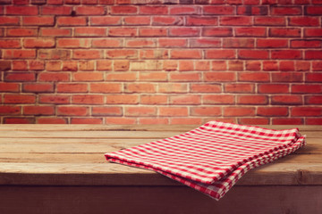 Wooden table with tablecloth over brick wall