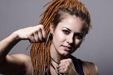 Close-up portrait young woman with dreadlocks in a fighting stan
