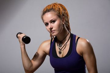 Portrait of a young girl with dreadlocks training with dumbbells