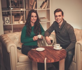 Young couple drinking coffee during discussion